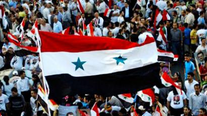 Thousands of Syrian citizens wave their national flags during a pro-government demonsration in Damascus (AFP Photo / HO-Sana)