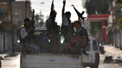 Syrian rebels raise their weapons during a patrol in the town of Tal Abyad (AFP Photo / Bulent Kilic)