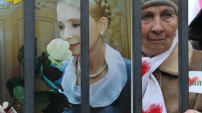 A supporter of Ukraine's former Prime Minister Yulia Tymoshenko holds a picture of the opposition leader during a mass rally in front of Ukrainian court in Kiev on December 13, 2011 (AFP Photo / Sergei Supinsky)