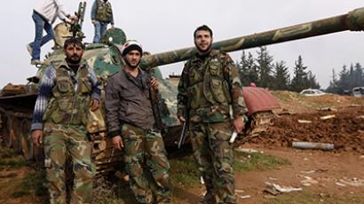 Free Syrian Army fighters pose at a tank after capturing the Military Infantry School following heavy clashes with forces loyal to President Bashar al-Assad in Aleppo December 16, 2012. (Reuters / Zain Karam)