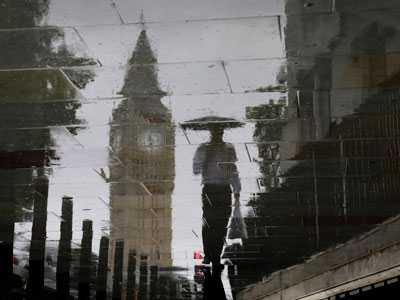 A pedestrian is reflected next to Big Ben on a wet pavement during a rainy day in central London.(REUTERS / Stefan Wermuth)
