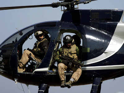 In a file picture dated 05 February 2005, members of the US-based Blackwater private security firm scan Baghdad city centre from their helicopter. Iraq's interior minister Jawad al-Bolani 17 September 2007 has ordered to cancel the licence of Blackwater, the US-based private security company, after it was involved in a shootout that killed eight people, an offical told AFP. (AFP Photo/Marwan Naamani)
