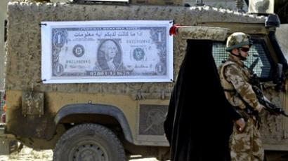 "A woman walks past a soldier standing guard next to a military vehicle with a poster of a US Dollar bill with the Arabic writing: ""You can get some money, in exchange for some information"" (AFP Photo)"