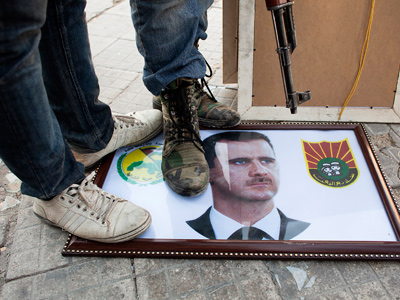 Syrian rebels stand on a picture of President Bashar al-Assad in the northern city of Aleppo on August 20, 2012. (AFP Photo/Achilleas Zavallis)