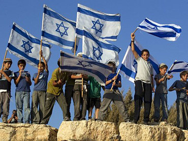 Israeli children wave the Israeli flag as hundreds of people have set out on a march in show of support for Jewish settlements from the settlement of Itamar in the Israeli occupied Palestinian West Bank to the Palestinian city of Nablus. (TOPSHOTS/AFP Photo/Jack Guez)