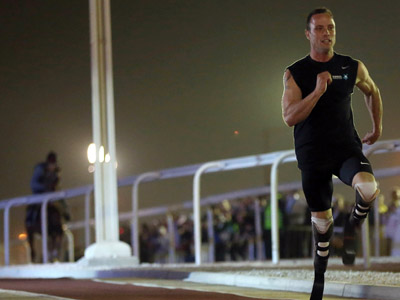 Paralympic and Olympic runner Oscar Pistorius of South Africa races against a pure-bred Arabian horse during the Gathering of all Leaders In Sport (GOALS) forum on December 12, 2012, at the Aspire Zone outdoor circuit in the Qatari capital Doha. (AFP Photo/Karim Jaafar/Al-Watan Doha)