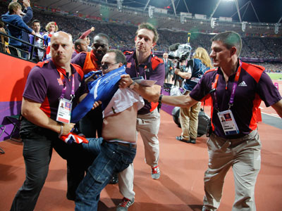 A man is detained by security shortly after an incident during the men's 100 metres final at the London 2012 Olympic Games.(REUTERS / Chris Helgren)