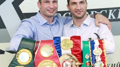 Wladimir and Vitaly Klitschko posing with their belts (RIA Novosti / Anton Denisov)