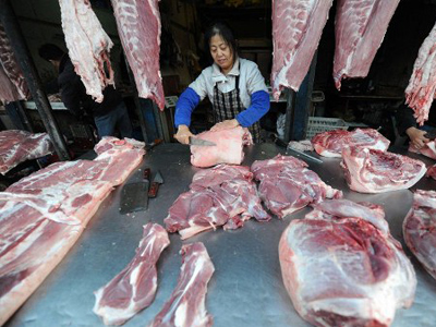 A Chinese pork seller waits for customers at his stall. (AFP Photo / China out)