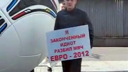 "The banner says: ""I'm a complete idiot – I broke the Euro 2012 ball"" (Still image from YouTube.com)"