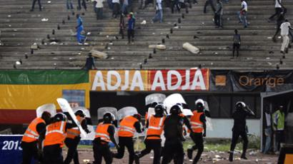 Police officers run with shields as Senegalese football fans throw rocks at them at Leopold Sedar Senghor stadium in Dakar October 13, 2012. (Reuters)