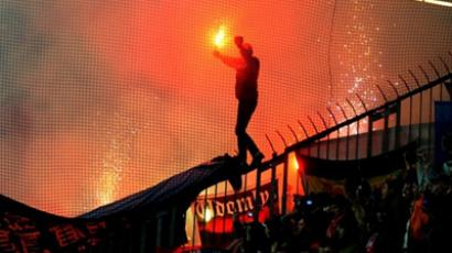 A Spartak Moscow fan holds a flare as he walks on security fencing during the group F UEFA Champion's league match between MSK ZIlina and Spartak Moscow in Zilina on December 8, 2010 (AFP Photo / Joe Klamar)