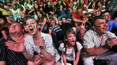 Fans react as they watch the final of the Euro 2012 football championships between Spain and Italy on a giant screen in the fan zone in Kiev on July 1, 2012. (AFP Photo/Genya Savilov)