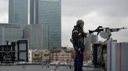 "A crew member stands guard next to a mounted gun as British Royal Navy helicopter carrier HMS Ocean passes Canary Wharf during security rehearsals, ""Exercise Olympic Guardian"", ahead of the London 2012 Olympic Games on the River Thames in east London (AFP Photo/ Ben Stansall)"