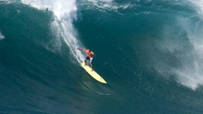 Professional surfer Garrett McNamara drops in on a large wave (Reuters/Hugh Gentry)