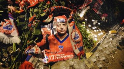 Yaroslavl : A portrait of Ivan Tkachenko, one of the players from the Lokomotiv Yaroslav ice hockey team thought to have perished in an air crash earlier in the day, is seen flanked by candles and glasses in front of Arena-2000, the team's home venue in Yaroslavl early on September 8, 2011. (AFP Photo / Alexander Nemenov)