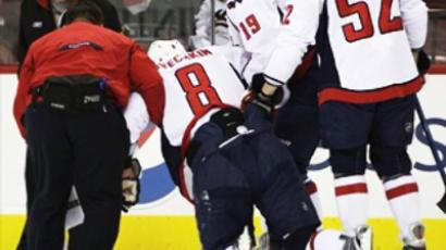 Washington Capitals' Alex Ovechkin is helped from the ice  after a collision with Carolina Hurricanes' Tim Gleason