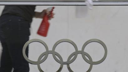An employee cleans a handrail above the Olympic logo at the IOC  (AFP Photo/ Sebastien Bozon)