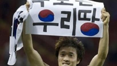 South Korea's Park Jong-woo holds up a banner after his team's win against Japan in bronze match at the London 2012 Olympics (AFP Photo / HO)