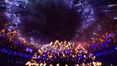Fireworks explode over the Olympic flame in the Olympic stadium in London during the closing ceremony of the 2012 London Olympic Games on August 12, 2012 (AFP Photo / Olivier Morin)