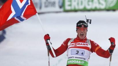 Tarjei Boe of Norway reacts, while waving his national flag, as he crosses the finish line in the mixed 2 x 6 + 2 x 7.5 km relay at the IBU Biathlon World Championships in Khanty-Mansiysk, March 3, 2011