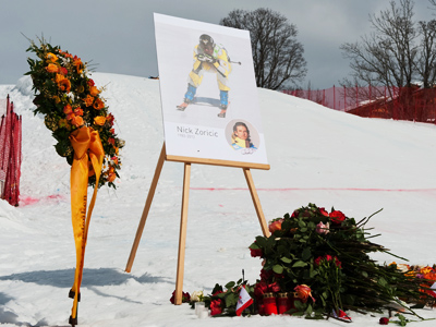 Flowers and a portrait are seen on the site where Canada's Nick Zoricic was deadly injured, in Grindelwald, March 11, 2012 (Reuters / Ernst Kehrli)