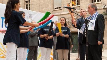 Former Sorbonne President, Georges Molini, (R) and the University's students light the Kazan 2013 Universiade flame (Image from http://kazan2013.ru)
