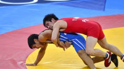 A picture taken on August 10, 2012 in London shows North Korea's Yang Kyong Il (R) fighting against Kazakhstan's Daulet Niyazbekov during their Men's 55kg Freestyle bronze medal match, part of the wrestling event of the London 2012 Olympic Games.  (AFP Photo/Yuri Cortez)
