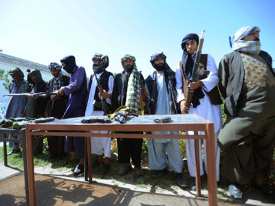 Taliban fighters stand near their weapons after they joined Afghanistan government forces during a ceremony in Herat on August 28, 2011 (AFP Photo / Aref Karimi)
