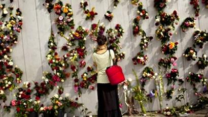 A woman is seen in front of wall decorated with flowers in memory of the victims of Friday's bomb attack and shooting rampage in Oslo, Norway, Tuesday, July 26, 2011