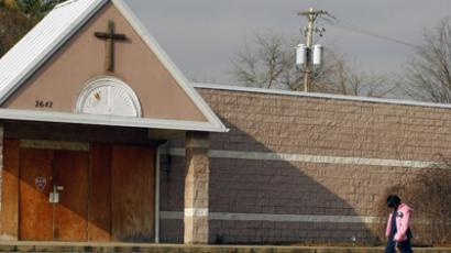 A woman walks past an empty, boarded-up church in Youngstown, Ohio (Reuters/Brian Snyder)