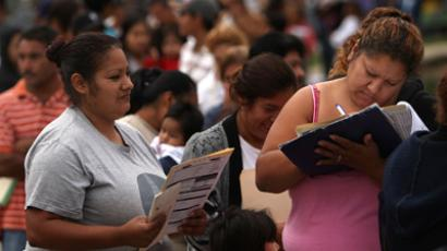 People fill out state forms for food stamps. (AFP Photo / Spencer Platt)