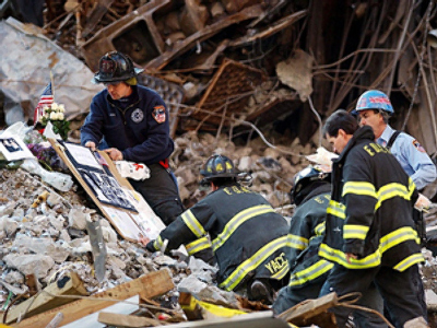 US, New York: City Firefighters place family photos and flowers at a makeshift memorial 28 October, 2001, on the rubble of ground zero after the World Trade Center Family Memorial Service in New York. Several thousand people attended the interfaith service near ground zero of the 11 September terrorist attack. (AFP Photo / Stan Honda)
