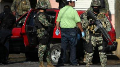 Mexican army soldiers stand guard around a car where a forensic team works on recovering corpses of alleged members of a drug cartel in Veracruz, on October 30, 2011 (AFP Photo / Lucas Castro)