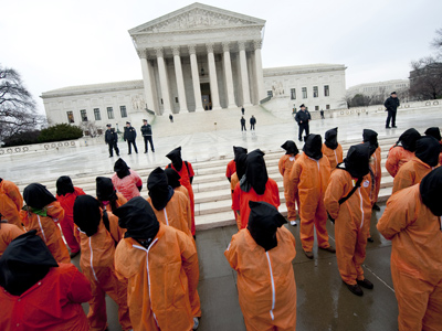Protesters wearing orange prison jump suits and black hoods on their heads march during a protest against holding detainees at the military prison in Guantanamo Bay during a demonstration in front of the US Supreme Court in Washington (AFP Photo)