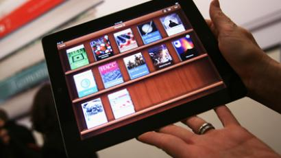 A woman holds up an iPad with the iTunes U app after a news conference introducing a digital textbook service in New York (Reuters/Shannon Stapleton/Files)
