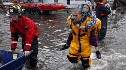 A rescue worker carries a boy on his back as emergency personnel rescue residents from flood waters brought on by Hurricane Sandy in Little Ferry, New Jersey October 30, 2012. (Reuters/Adam Hunger)