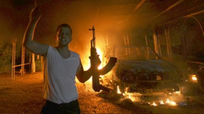 A protester reacts as the U.S. Consulate in Benghazi is seen in flames during a protest by an armed group said to have been protesting a film being produced in the United States September 11, 2012. (Reuters/Esam Al-Fetori)