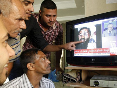 A news broadcast on Arabic satellite news channel Al-Arabiya showing an image which has been circulating on the internet and allegedly shows the body of Al-Qaeda mastermind Osama bin Laden, on May 2, 2011 (AFP Photo / Sabah Arar)