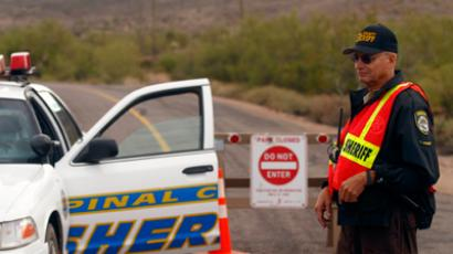 A Pinal County Sheriff volunteer police officer blocks a road leading to the Superstition Mountains where rescue workers search for victims of a plane that crashed in Apache Junction, Arizona (Reuters/Joshua Lott)
