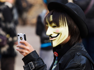 A person wears a Guy Fawkes mask while using an Apple iPhone at the Occupy Toronto movement in Toronto. (REUTERS/Mark Blinch)