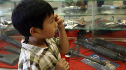 A boy, accompanying his father, looks at weapons for sale at the Gun Gallery in Glendale, California. (AFP Photo)