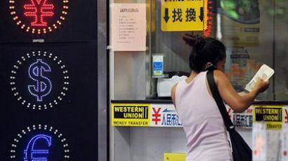 A woman exchanges money at a currency exchange shop in Hong Kong on September 15, 2011. (AFP Photo / Laurent Fievet)
