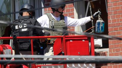 Law enforcement officers put a container filled with blue liquid to use in an explosion at the apartment where suspect James Eagan Holmes lived in Aurora, Colorado July 21, 2012 (Reuters / Joshua Lott)