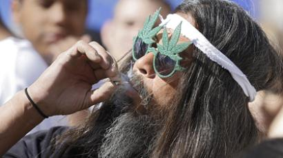 Fast Eddy Aki'a of Hawaii smokes a joint as thousands gathered to celebrate the state's medicinal marijuana laws in Civic Center Park April 20, 2012 in Denver, Colorado. (AFP Photo / Marc Piscotty)