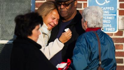 A woman leans on a man as she weeps outside a building set up to counsel family members affected by a shooting nearby at Sandy Hook Elementary School in Newtown, Connecticut, December 14, 2012 (Reuters / Lucas Jackson)