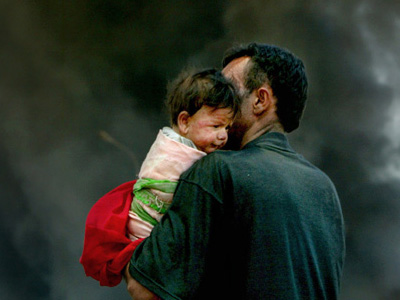 Abdul Hussein Hasan holds his 10-month-old son away from a burning oil dump near their house in a former Iraqi army camp in the outskirts of Baghdad April 29, 2003. (REUTERS/Yannis Behrakis YB)