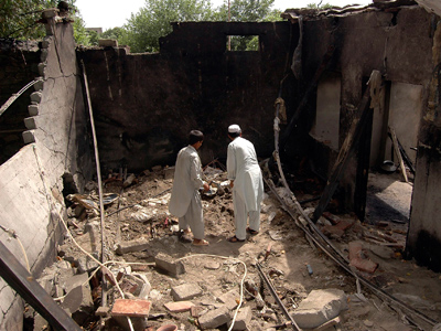 Residents stand inside a damaged house after a missile attack in Damadola village of the Bajaur tribal region in Pakistan (Reuters / Ammad Waheed)