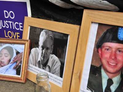 United Kingdom, London: Supporters of Wikileaks founder Julian Assange display photographs of Assange and US serviceman Bradley Manning outside the High Court in central London, on July 12, 2011. (AFP Photo / Leon Neal)