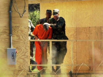 A US Army MP holds down the head of a detainee so he is not identified 14 Febuary 2002 as the detainee is taken inside one of four Joint Interrogation Facilities at Campa X-Ray in Guantanamo Bay, Cuba (AFP Photo / Peter Muhly)